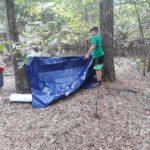 folding up a tarp at camp